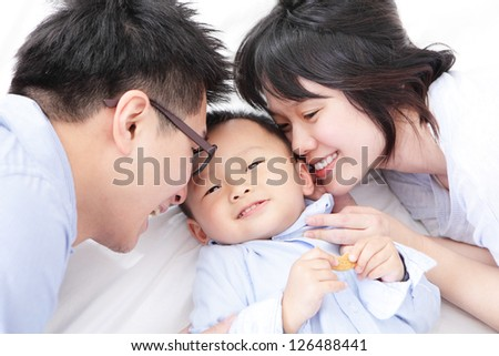 Happy family with children in bed, asian people - stock photo