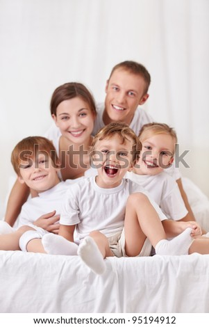 Happy family with children in the bedroom - stock photo
