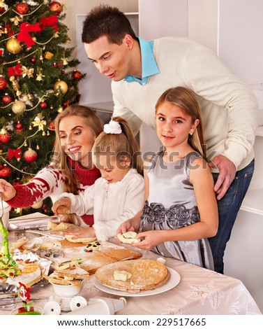 Happy family with children rolling dough in Christmas kitchen. - stock photo