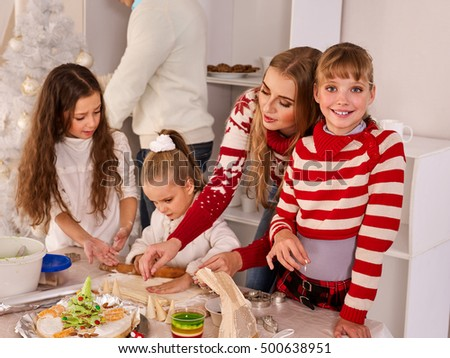 Happy family with children rolling dough in Christmas kitchen. Happy family learn cooking Xmas food.