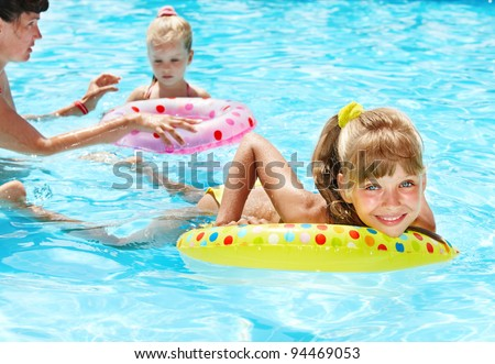 Happy family with children sitting on inflatable ring in swimming pool. - stock photo
