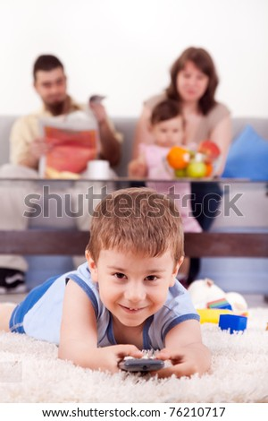 happy family with children sitting on sofa and  watching TV at home - stock photo