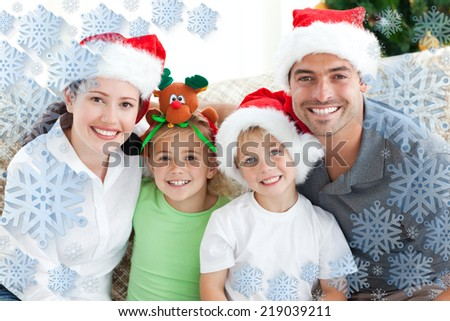 Happy family with christmas hats sitting on the sofa against snowflake frame - stock photo