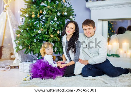 Happy family with Christmas present near the Christmas tree - stock photo