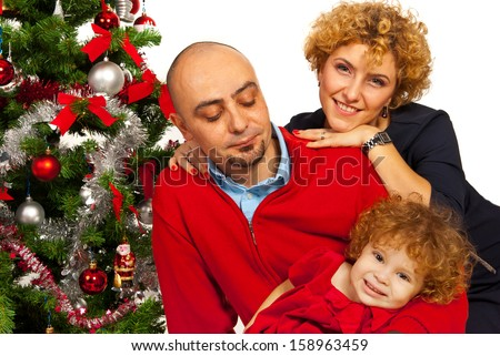 Happy family with Christmas tree standing together in their home - stock photo