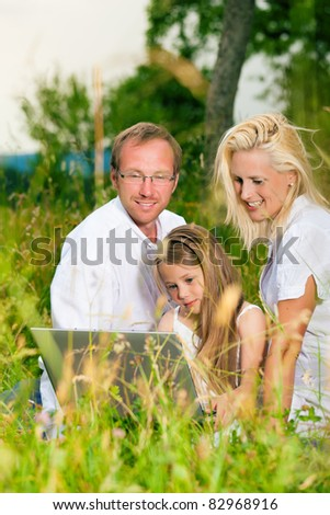 Happy family with daughter girl sitting in a meadow in summer with laptop