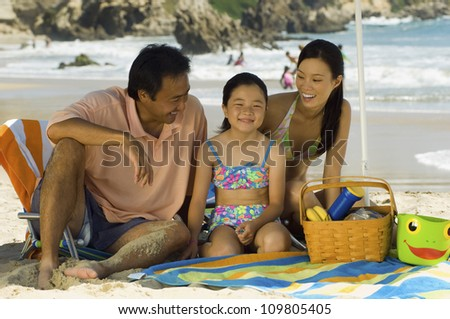Happy family with daughter on a beach vacation - stock photo