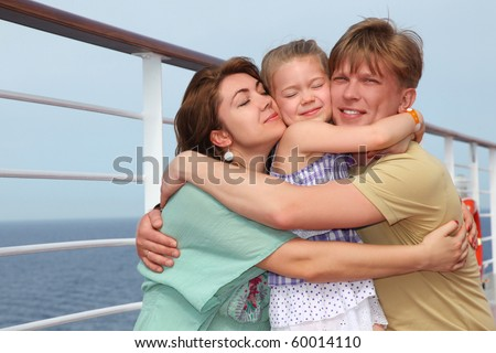 happy family with daughter on cruise liner deck embracing each other, half body