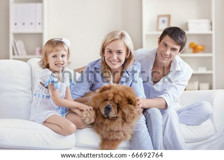 Happy family with dog at home - stock photo