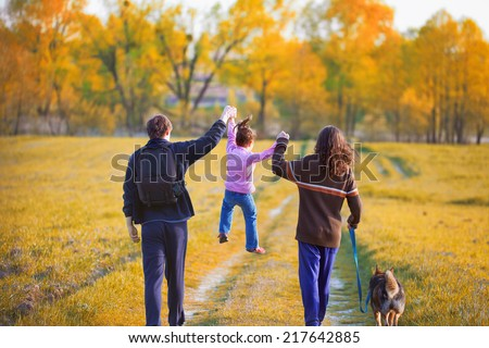 Happy family with dog walking in the field back to camera - stock photo