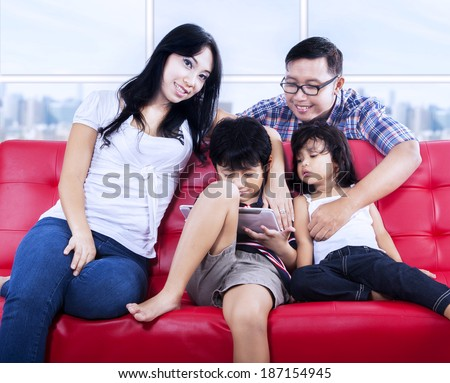 Happy family with e-tablet enjoying quality time at apartment on red sofa - stock photo