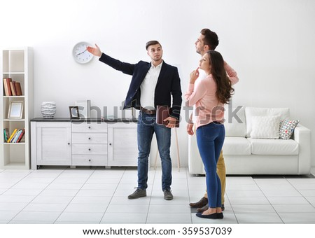Happy family with estate agent,  in new home - stock photo