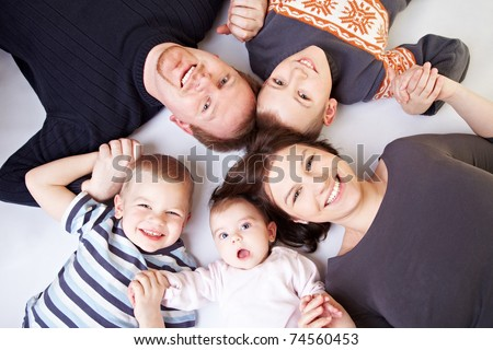 Happy family with father and mother and three children including baby girl - stock photo