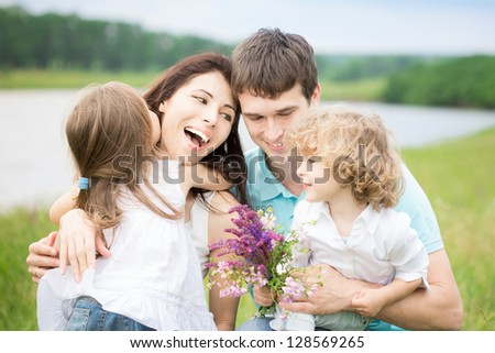 Happy family with flowers having fun outdoors in spring field - stock photo