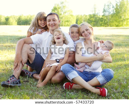 Happy family with four children in park