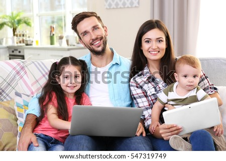 Happy family with gadgets on couch