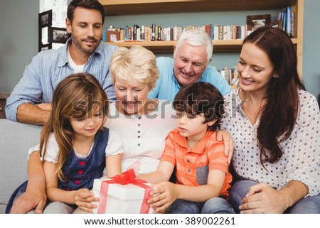 Happy family with gift box at home - stock photo