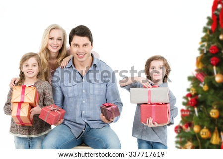 Happy family with gifts near a Christmas tree celebrating 2016 New year, Christmas at home. - stock photo