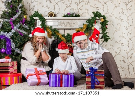 Happy family with  gifts sitting near Christmas tree at home. - stock photo