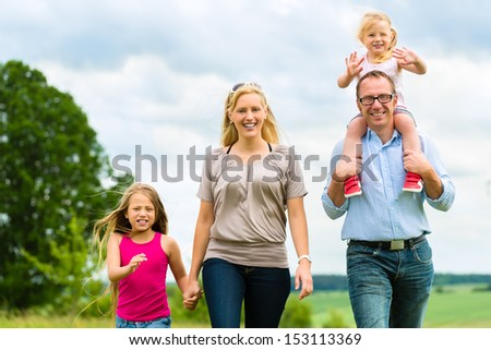 Happy Family with girls or daughters walking in a meadow in summer - stock photo