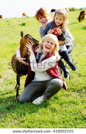 happy family with goat on the green meadow