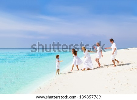 Happy family with grandparents, young couple and child playing on a beach