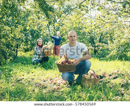 Happy family with  harvested apples in garden