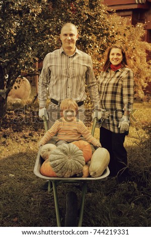 Happy  family with harvested pumpkins in garden
