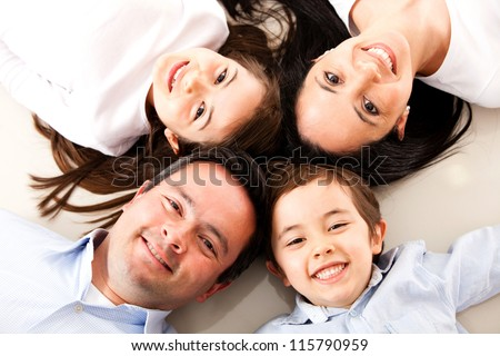 Happy family with heads together on the floor - stock photo