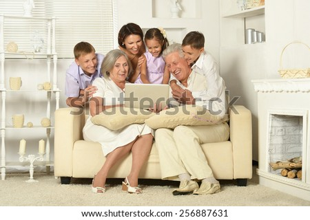 Happy family with kids and laptop on couch in living room - stock photo