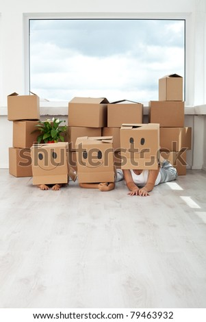 Happy family with kids having fun among cardboard boxes in their new home - stock photo