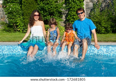 Happy family with kids having fun near pool on summer vacation
