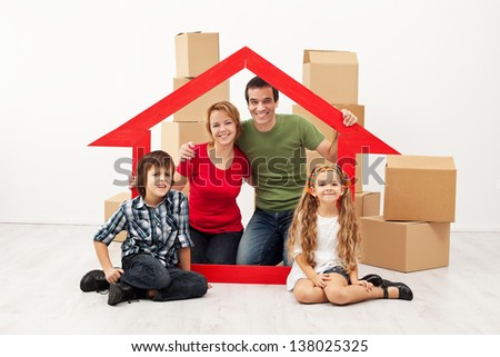 Happy family with kids moving into a new home - sitting with cardboard boxes - stock photo