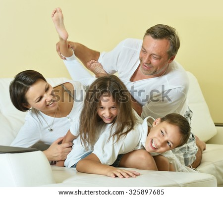 Happy family with kids on couch in living room