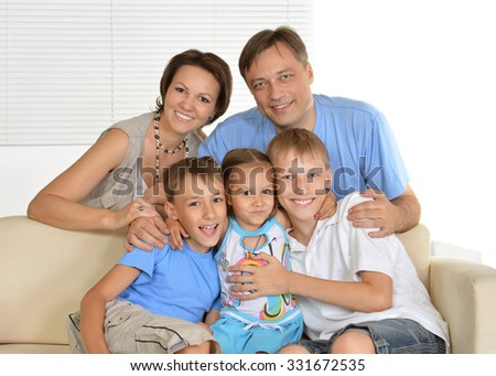 Happy family with kids on couch in living room - stock photo