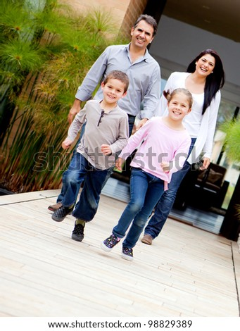 Happy family with kids running outside their house - stock photo