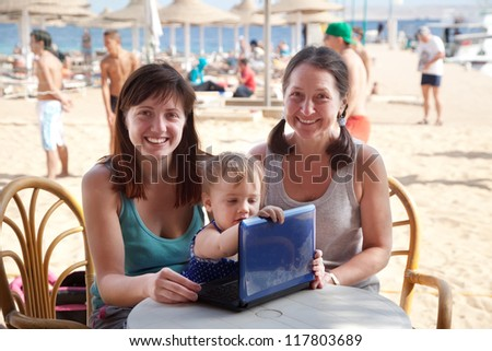happy family  with laptop  at resort  beach - stock photo