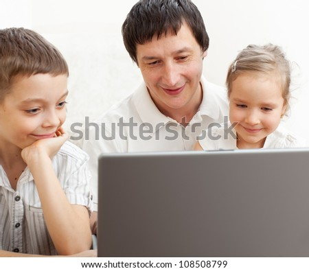 Happy family with laptop. Father with children play in the computer