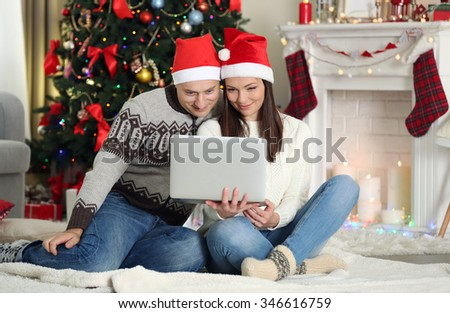 Happy Family with laptop on Christmas tree background