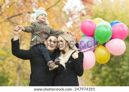 happy family with little child and air-balloons, outing in autumn park - stock photo