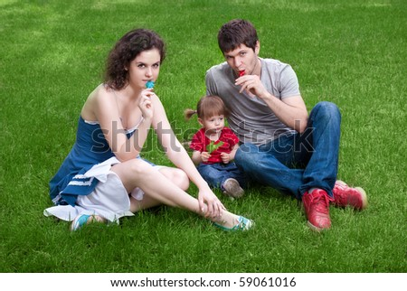 Happy family with little daughter sitting on green grass in park