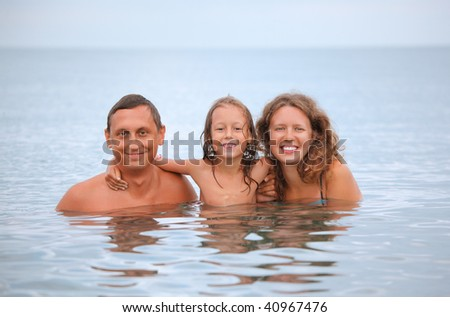 Happy family with little girl bathe in sea - stock photo