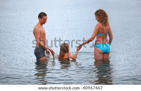 Happy family with little girl bathe in sea, standing back - stock photo