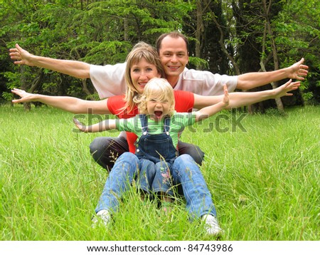 Happy family with little girl having fun on meadow - stock photo