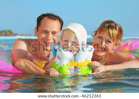 Happy family with little girl in white hat and life-jacket bathing in pool against sea - stock photo