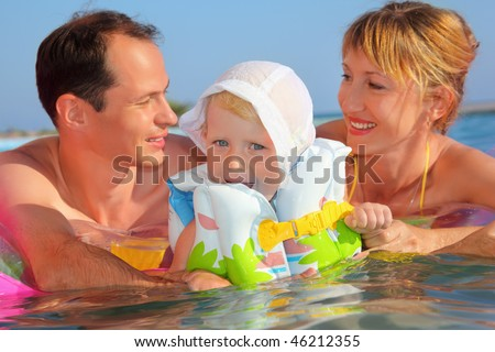 Happy family with little girl in white hat and life-jacket bathing in pool against sea, Parents looking against each other - stock photo
