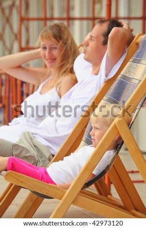 Happy family with little girl reclining on chaise lounges on veranda - stock photo
