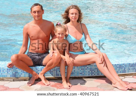 Happy family with little girl sit near in pool - stock photo