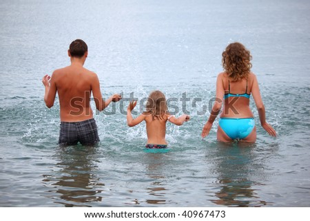 Happy family with little girl splashes water hands standing on belt in sea, standing back - stock photo