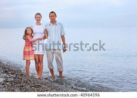 Happy family with little girl standing on beach in evening